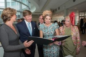 Koning Willem-Alexander en koningin Máxima bekijken het boek Koningsdamast met het essay Van Boom tot Tafel